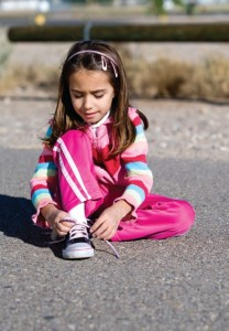 Little girl tying shoe